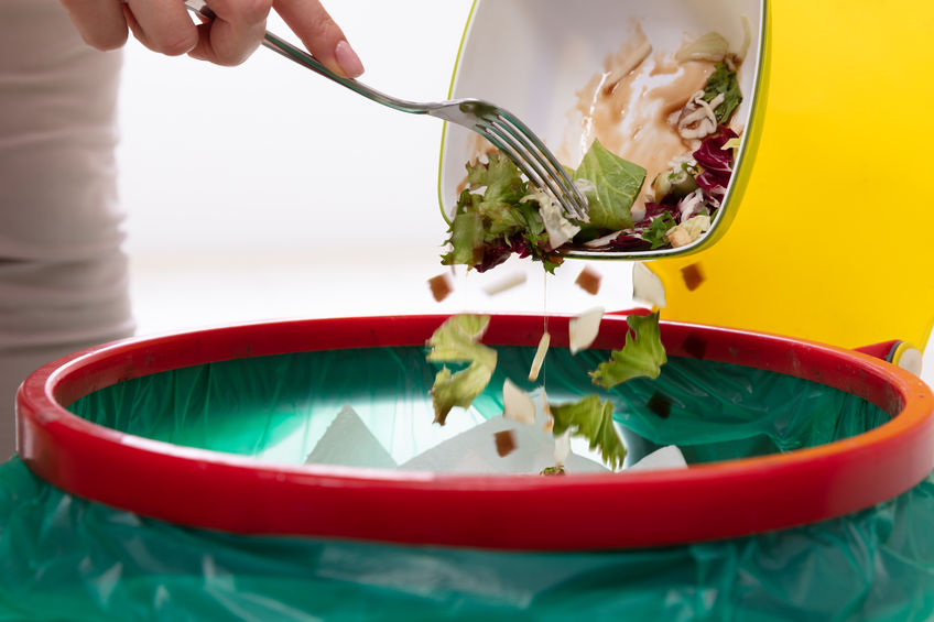 Domestic Food Waste; Woman Throwing Vegetables In Trash Bin